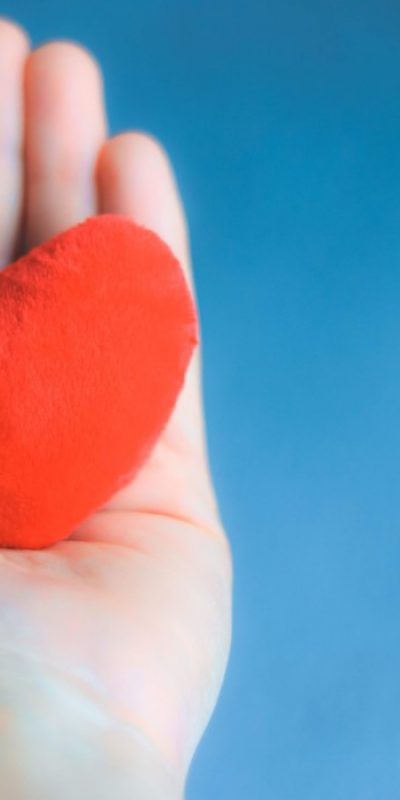 close-up-shot-of-hand-holding-soft-red-heart-on-blue-background-happy-valentine-love-care_t20_983EaO.jpg